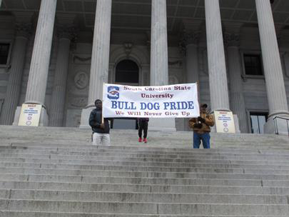 Supporters of South Carolina State University hold up a banner at a Statehouse rally against a proposal to close South Carolina State University on Feb. 16, 2015, in Columbia, S.C. Supporters are now suing the state over unequal funding. (AP Photo/Jeffrey Collins)