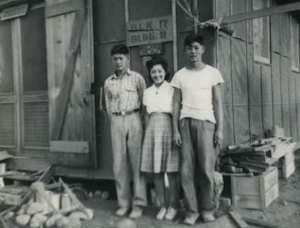 Japanese Americans outside of one of the structures at an internment camp during World War II. (Photo courtesy of California State University Japanese American Digitization Project)