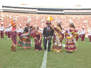 Tribal members crown the homecoming chief and princess with authentic Seminole regalia at Florida State University.