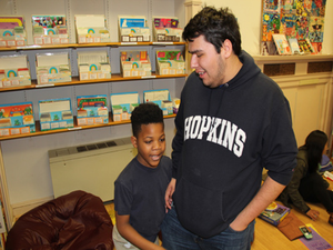 Matthew Rios, a freshman neuroscience and psychology major from Long Beach, California, is helping Malik with multiplying two-digit numbers.